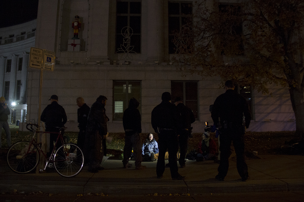Police officers talk to Terese Howard as they give her warnings to vacate. Protesters who have set up camp in front of the City and County Building to denounce Denver's urban camping ban are removed by police. Nov. 29, 2016. (Kevin J. Beaty/Denverite)  camping ban; right to rest; homeless sweeps; city and county building; police; protest; kevinjbeaty; denver; denverite; colorado;