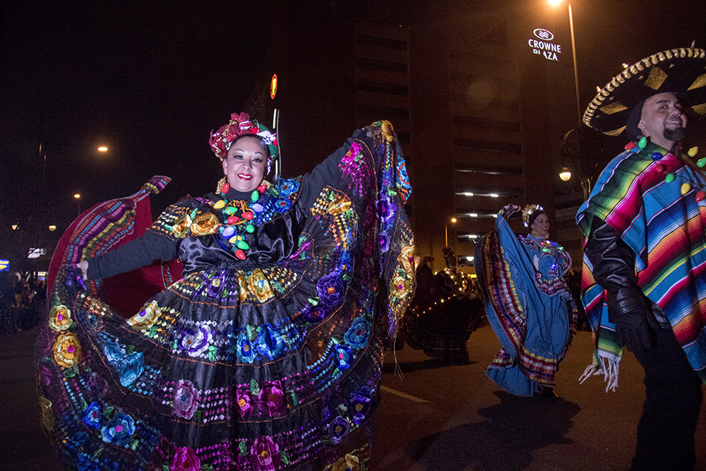 """Dancers twirl to """"Feliz Navidad."""" Parade of lights. Dec. 2, 2016. (Kevin J. Beaty/Denverite)parade of lights; holiday; christmas; civic center; kevinjbeaty; denver; denverite; colorado;"""