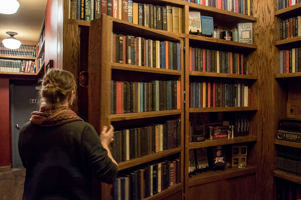 Alex Bair opens a bookshelf for a secret passage to Williams and Graham. (Chloe Aiello/Denverite)  Williams and Graham; speakeasy; bar; Highlands