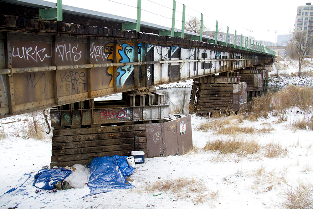 A man sleeps under a tarp under a train bridge near City of Cuernavaca Park. (Kevin J. Beaty/Denverite)  right to rest; camping ban; homeless; cowx; weather; cold; snow; winter; kevinjbeaty; denver; colorado; denverite;