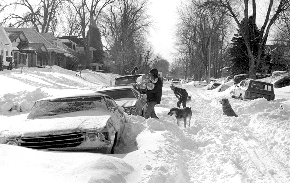 A man carries logs, others shovel snow near 2377 Elm Street in the South Park Hill neighborhood of Denver, Colorado after the 1982 snowstorm. (Allison St. Claire/Denver Public Library/Western History Collection/X-29024)  archive; archival; historic; denver public library; dpl; western history collection; blizzard; snowstorm; weather; cowx; denverite; denver; colorado;