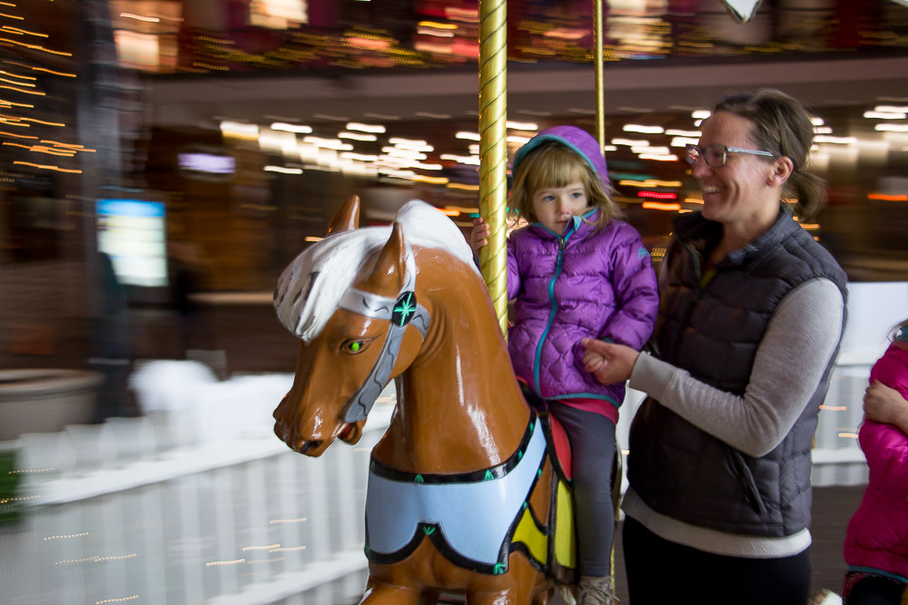 Ellery and Christin Crosby ride the Denver Pavilions holiday carousel. (Chloe Aiello/Denverite)