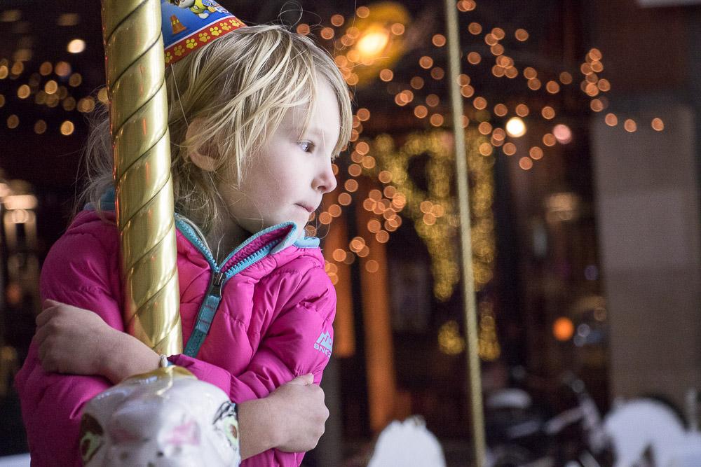 Eden Crosby at the Denver Pavilions holiday carousel. (Chloe Aiello/Denverite)