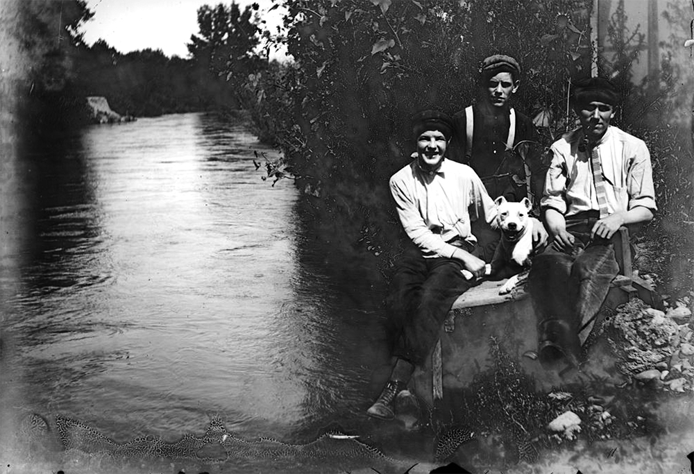 Outdoor portrait of two men, a woman, and dog near the edge of Archer Canal in Denver, Colorado. (Denver Public Library/Western History Collection/CHS-L2427)