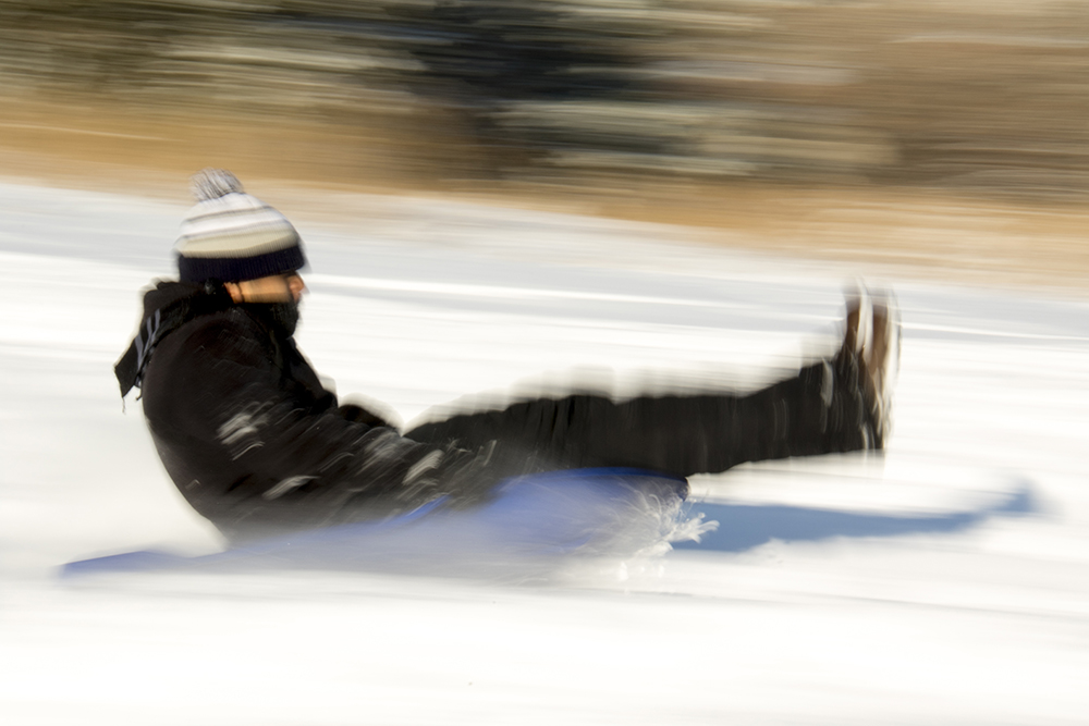 Daniel Esparza zips down Ruby Hill on a sled. Dec. 17, 2016. (Kevin J. Beaty/Denverite)  snow day; winter; sledding; denver; denverite; colorado; kevinjbeaty;