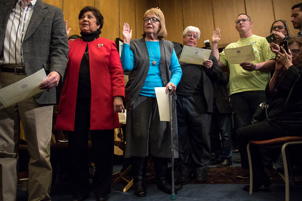 Electors Polly Baca, Anne Hallman, Robert Nemanich and Micheal Baca take their oaths in Governor Hickenlooper's office at the Colorado Capitol. (Chloe Aiello/Denverite)