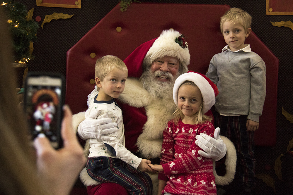 Kate Haggerty photographs Connor (left to right), Evelyn and Max with Santa. Christmas Eve at Union Station, 2016. (Kevin J.Beaty/Denverite)  union station; santa; christmas eve; holidays; downtown; kevinjbeaty; denver; denverite; colorado;