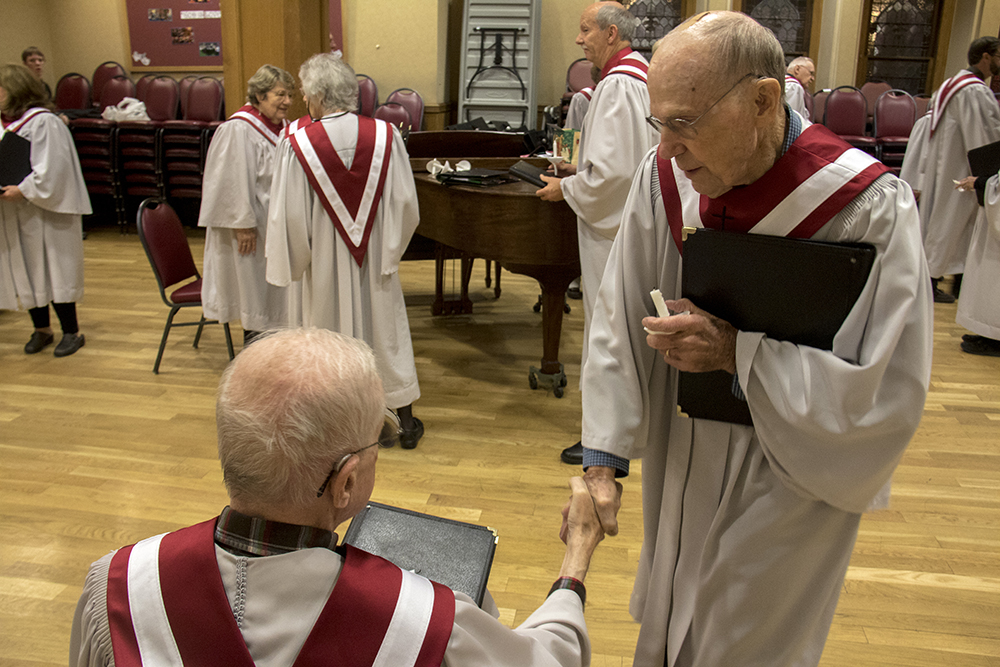 Hank Echert (left) and Tom Campman shake hands before the 7 P.M. service. Christmas Eve at Trinity United Methodist Church, 2016. (Kevin J.Beaty/Denverite)  christmas eve; holidays; downtown; kevinjbeaty; denver; denverite; colorado;