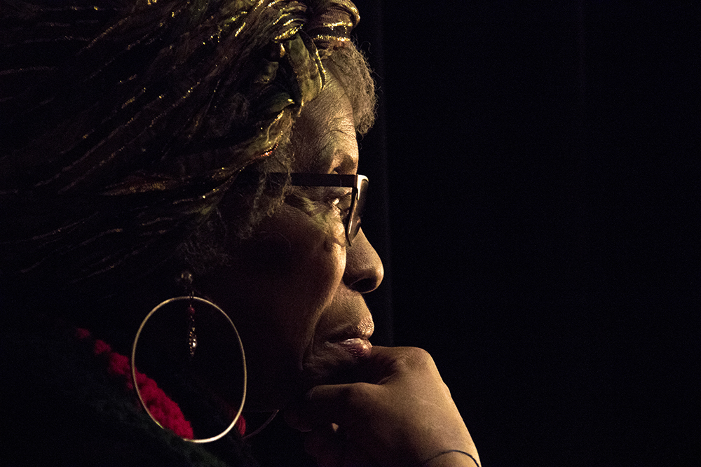 Esteemed elder Ms. Isetta Crawford Rawls watches from behind the curtain. The first night of Kwanzaa at the Cleo Parker Robinson Dance Theatre, Dec. 26, 2016. (Kevin J. Beaty/Denverite)  kwanzaa; Cleo Parker Robinson Dance Theatre; holidays; denver; denverite; kevinjbeaty; colorado; five points;