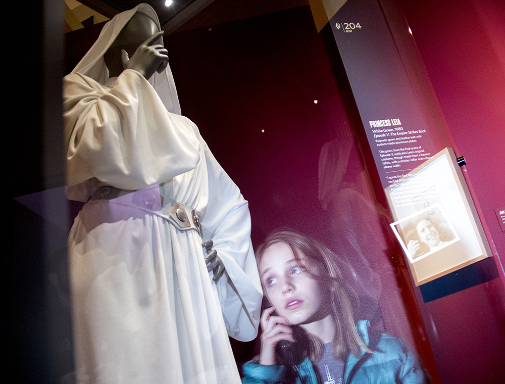 May Mackenzie stares up at a Princess Leia costume on exhibit at the Denver Art Museum. (Kevin J. Beaty/Denverite)  carrie fisher; star wars; denver art museum; dam; kevinjbeaty; denver; denverite; colorado;