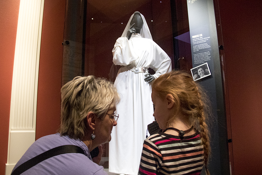 4-year-old Sammi Brooks and her grandmother Deb Johnson listen to audio tour clips in front of a Princess Leia costume at the Denver Art Musuem. (Kevin J. Beaty/Denverite)  carrie fisher; star wars; denver art museum; dam; kevinjbeaty; denver; denverite; colorado;