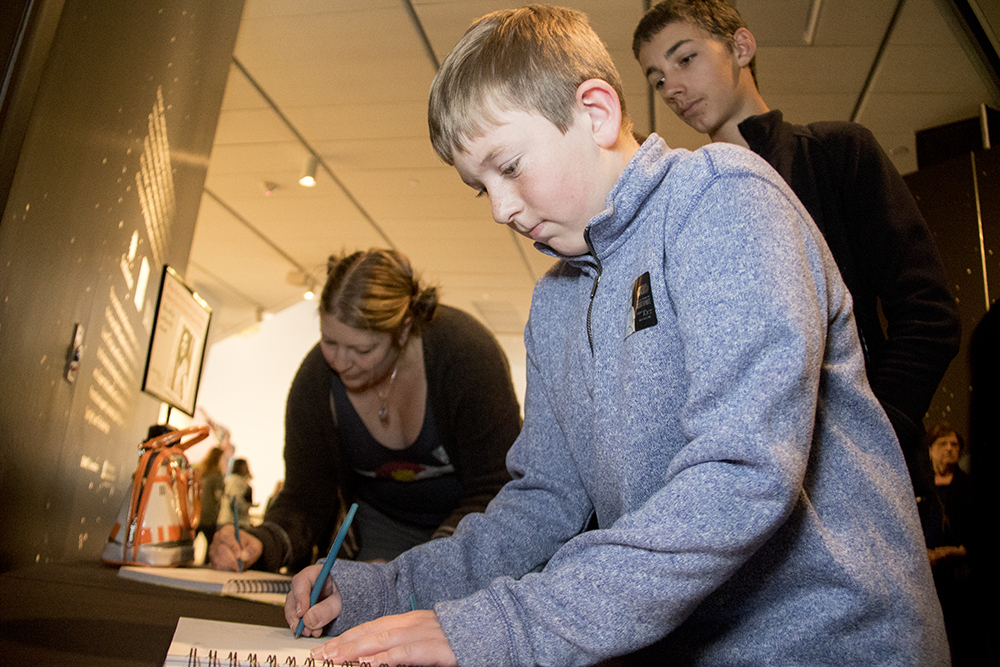 Jack Raugewitz writes a note for Carrie Fisher at the Denver Art Museum. (Kevin J. Beaty/Denverite)  carrie fisher; star wars; denver art museum; dam; kevinjbeaty; denver; denverite; colorado;