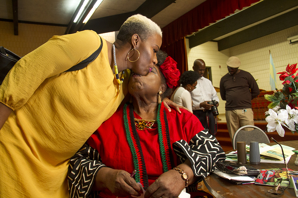 Dr. Claudette Sweet, program committee chair for the Kwanzaa Committee of Denver, kisses author Aziziah Jones after the 2016 Kwanzaa Elders Luncheon at Zion Senior Center in Northeast Park Hill. Dec. 28, 2016. (Kevin J. Beaty/Denverite)  kwanzaa; culture; kevinjbeaty; denver; denverite; northeast park hill; colorado;