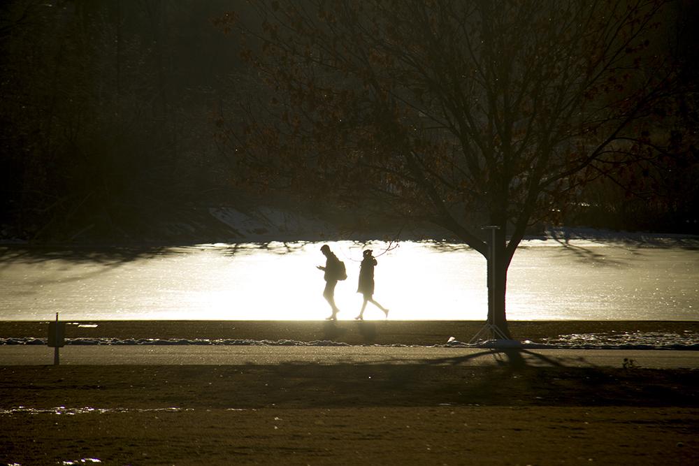 A couple walk by the frozen Ferril Lake in City Park. (Kevin J. Beaty/Denverite)  city park; denver; denverite; colorado; winter; kevinjbeaty;