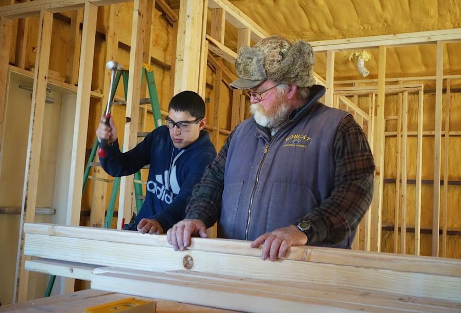 Ray Perez, a sophomore at Custer County High School, works with instructor Bruce May on a project that will convert a former preschool building into teacher housing. (Courtesy of Mark Payler)