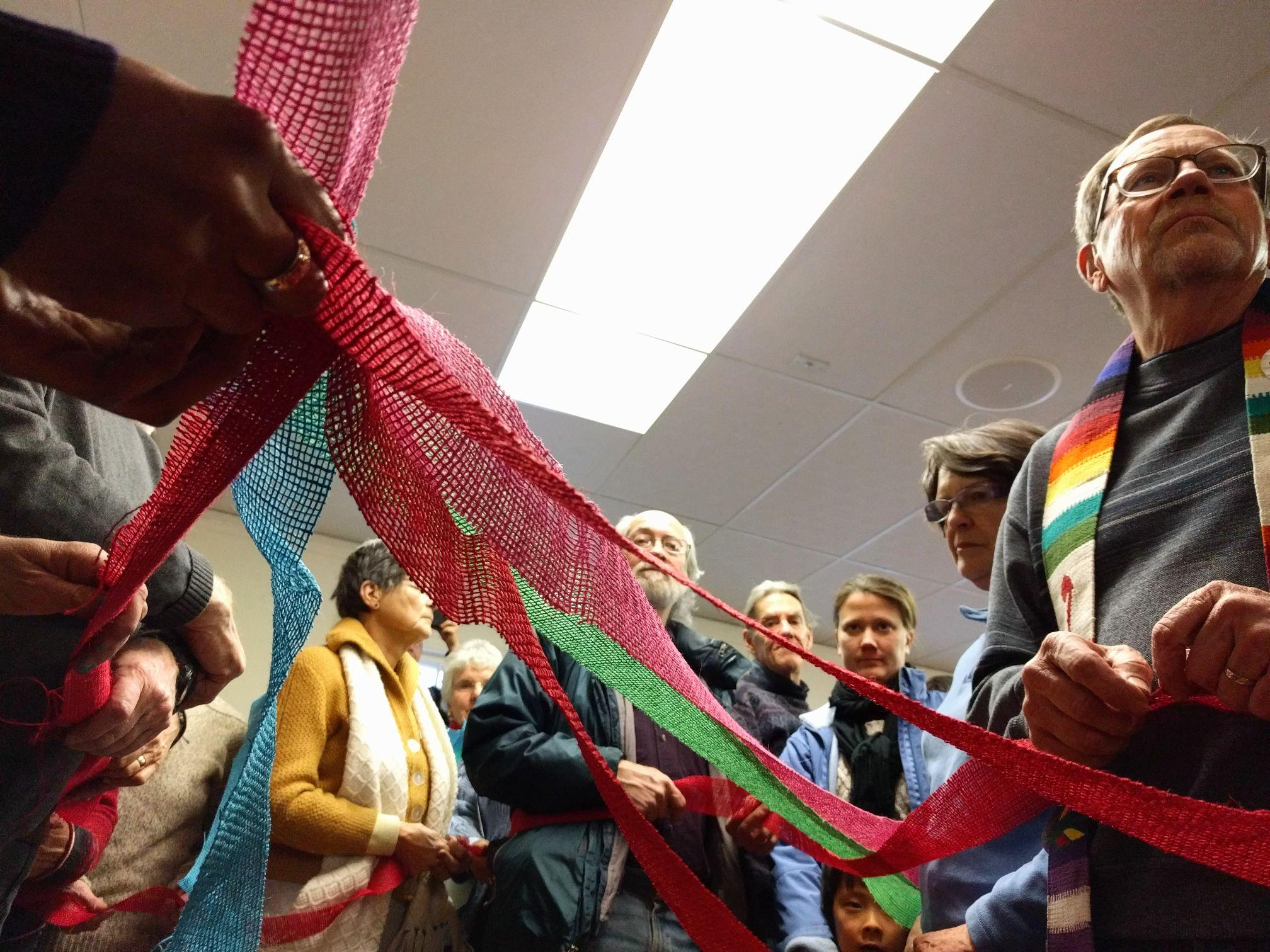 People who gathered to support Ingrid Encalada Latorre stand in a quaker circle holding a ribbon that symbolized their interconnection. That's Latorre's hands holding the nexus of ribbons on the top left. (Kevin J. Beaty/Denverite)