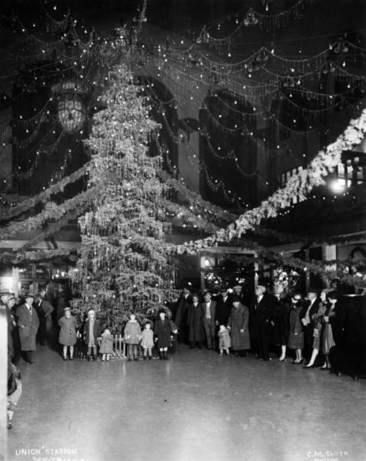 Interior view of the Union Station, in Denver, Colorado. Children, women, and men pose by a Christmas tree, garlands, and decorations. (Denver Public Library/Western History Collection/X-25208)