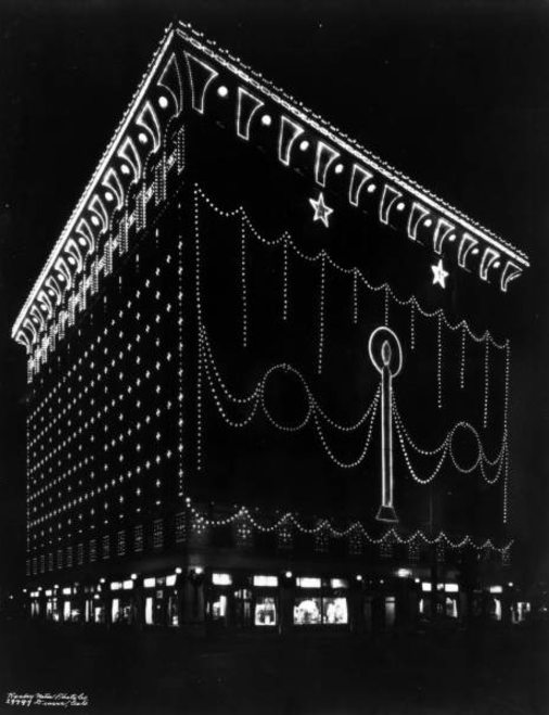 Nighttime view of the Gas and Electric Building at 15th and Champa Streets in downtown Denver, Colorado. The building is decorated with light bulbs for Christmas. (Denver Public Library/Western History Collection/X-24888)