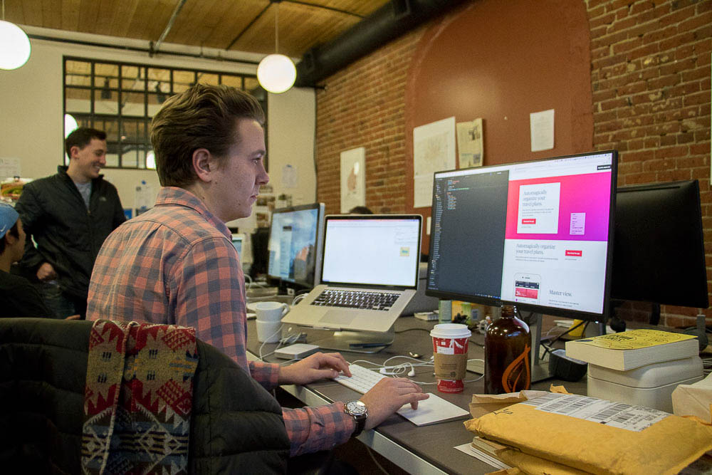 Devon Tivona, co-founder of Pana, works at his market street desk. (Chloe Aiello/Denverite)