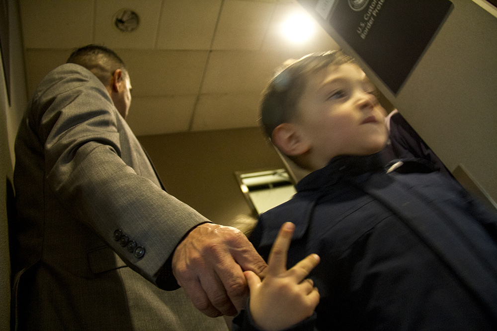 Isidro Quintana holds his grandson Remyi's hand as he waits for Homeland Security to answer him at DIA, Jan. 5, 2017. (Kevin J. Beaty/Denverite)  isidro quintana; kevinjbeaty; denverite; denver; colorado; immigration; deportation