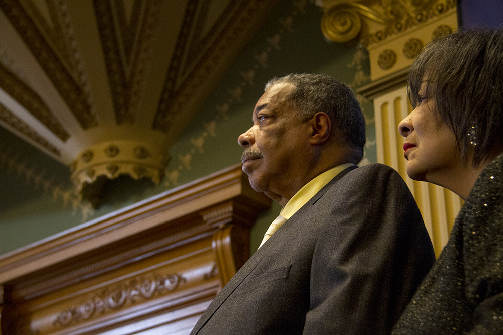 Wellington and Wilma Webb stand on the side of the House Chamber on the first day of the Colorado state legislative session. Jan 11, 2017. (Kevin J. Beaty/Denverite)