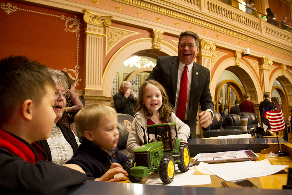 District 1 Senator Jerry Sonnenberg laughs as he hands a toy tractor, a fixture on his desk, to the family of Senate President Kevin Grantham. The first day of the Colorado state legislative session. Jan 11, 2017. (Kevin J. Beaty/Denverite)  legislature; copolitics; politics; legislative session; capitol; kevinjbeaty; denver; denverite; colorado;