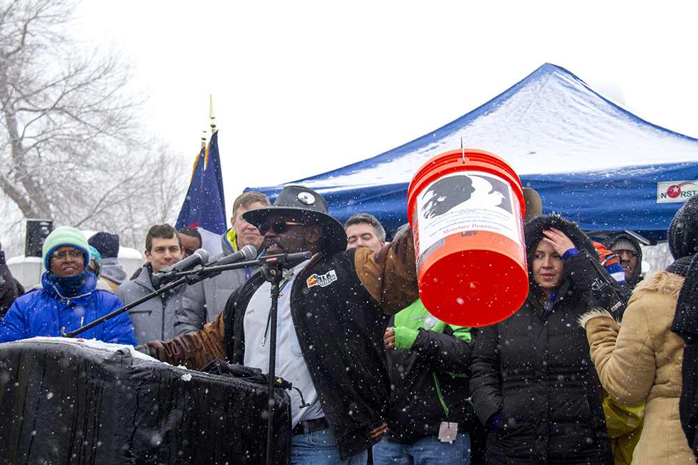 Long-time Martin Luther King Jr. Marade Chair Vern Howard holds up a bucket for donations, the first time collections have been made in the event's history. Jan. 16, 2017. (Kevin J. Beaty/Denverite)  mlk; marade; martin luther king jr; city park; denver; colorado; kevinjbeaty;