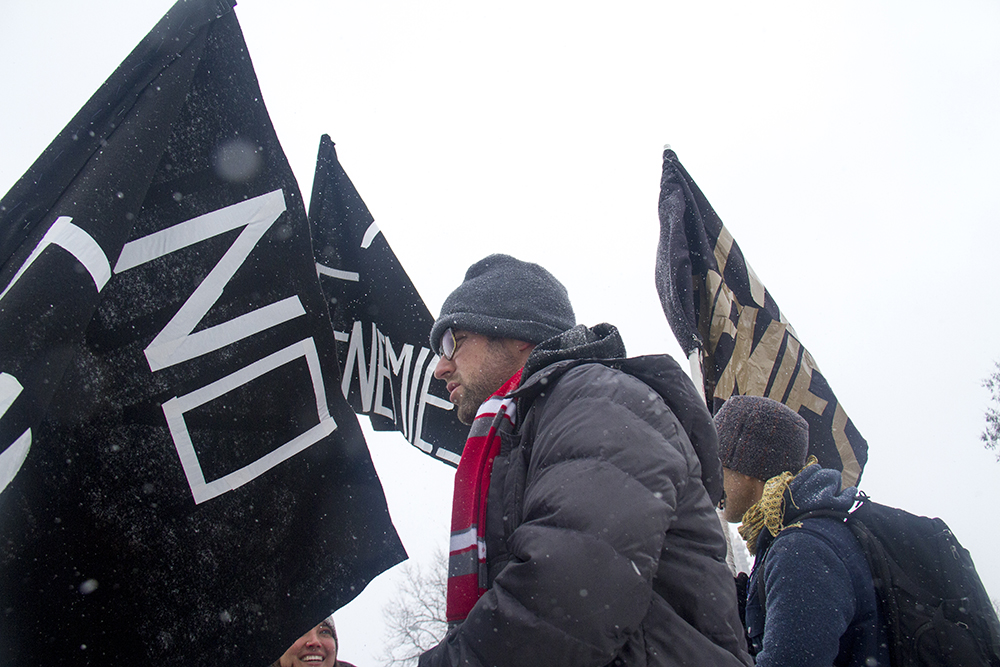 """Jamie """"Jonny 5"""" Laurie stands amongst flags reading """"No Enemies,"""" the name of the movement he co-founded and (also the forthcoming Flobots album) that tries to realize music as an avenue to achieve social change. Jan. 16, 2017. (Kevin J. Beaty/Denverite)  mlk; marade; martin luther king jr; city park; denver; colorado; kevinjbeaty;"""