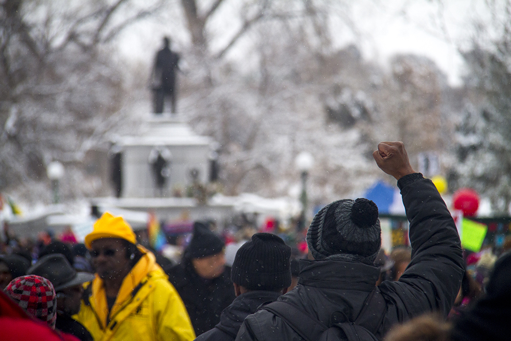 Brother Jeff Fard raises a fist as the Martin Luther King Jr. Marade begins. Jan. 16, 2017. (Kevin J. Beaty/Denverite)mlk; marade; martin luther king jr; city park; denver; colorado; kevinjbeaty; weather; cowx;