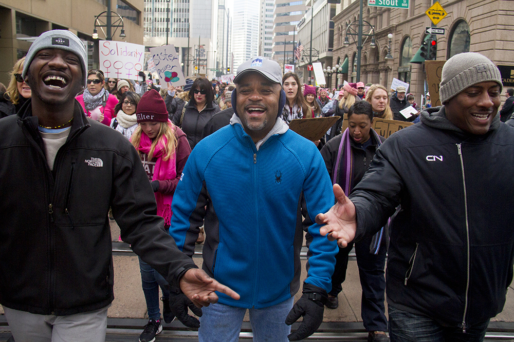 Mayor Michael Hancock and his companions laugh in unison during the Women's March on Denver. Jan. 21, 2017. (Kevin J. Beaty/Denverite)