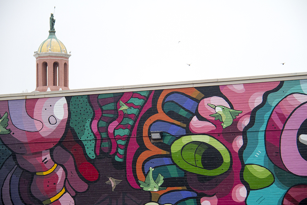 A mural before Casa Bonita's unmistakable steeple. The 40 West Arts District. (Kevin J. Beaty/Denverite)  40 west arts district; west colfax; lakewood; bid; kevinjbeaty; denverite; colorado; denver;
