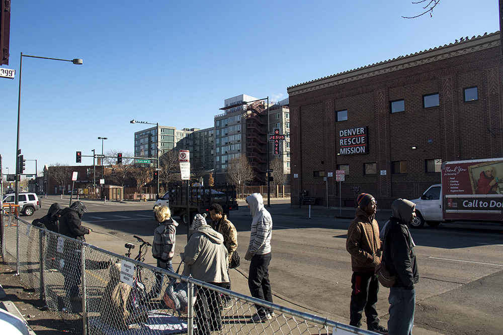 People stand across the street from the Denver Rescue Mission. (Kevin J. Beaty/Denverite)