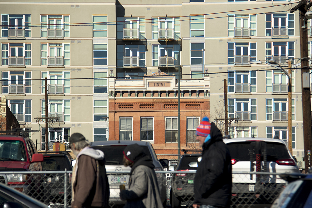 David McCleve, who stays at the Denver Rescue Mission (right), walks before apartment buildings. (Kevin J. Beaty/Denverite)  ballpark; five points; development; homeless;