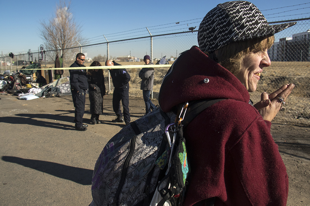 """Amanda Berry stands to the side as city workers """"sweep"""" a homeless encampments at Denargo and Delgany Streets where she was staying for two months, Jan. 26, 2016. (Kevin J. Beaty/Denverite)  homelessness; sweeps; right to rest; denver; colorado; kevinjbeaty; denverite;"""