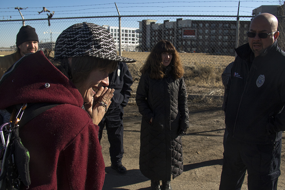 "Amanda Berry (left) speaks to Denver Animal Protection sergeant Stephen Romero as city workers ""sweep"" a homeless encampments at Denargo and Delgany Streets, Jan. 26, 2016. (Kevin J. Beaty/Denverite)  homelessness; sweeps; right to rest; denver; colorado; kevinjbeaty; denverite;"