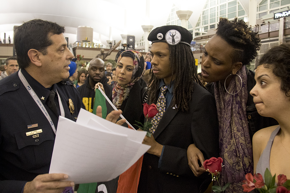 Commander Tony Lopez tells protesters that first amendment expressions without a permit are not allowed at DIA, Jan. 28, 2017. (Kevin J. Beaty/Denverite)  amal kassir; immigration; refugees; politics; protest; copolitics; rally; dia; denver; colorado; kevinjbeaty;