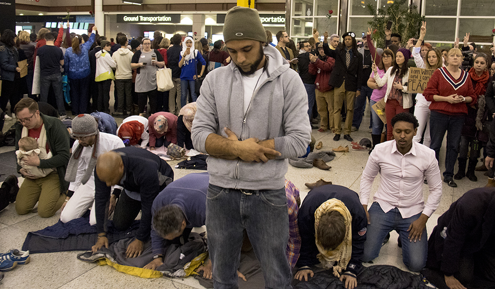 Muslim protesters pray at DIA, Jan. 28, 2017. (Kevin J. Beaty/Denverite)  amal kassir; immigration; refugees; politics; protest; copolitics; rally; dia; denver; colorado; kevinjbeaty;
