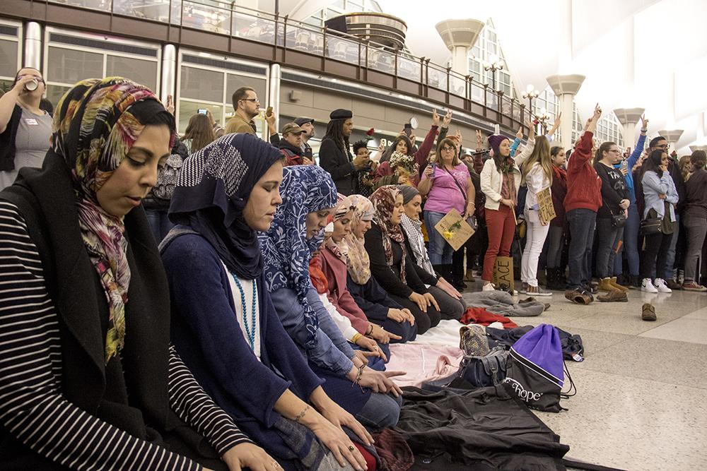 Muslim protesters pray at DIA, Jan. 28, 2017. (Kevin J. Beaty/Denverite)  amal kassir; immigration; refugees; politics; protest; copolitics; rally; dia; denver; colorado; kevinjbeaty;