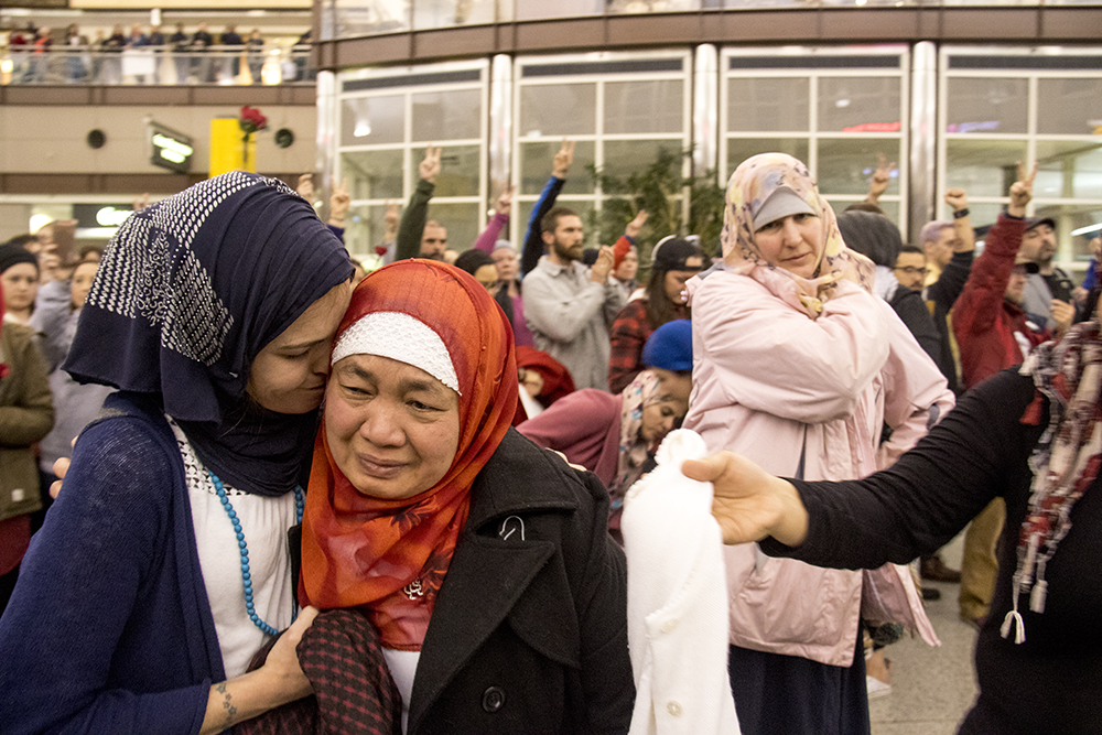 Desiree Winess (left) comforts dismayed Samoah Soulong during protests at DIA, Jan. 28, 2017. (Kevin J. Beaty/Denverite)  amal kassir; immigration; refugees; politics; protest; copolitics; rally; dia; denver; colorado; kevinjbeaty;