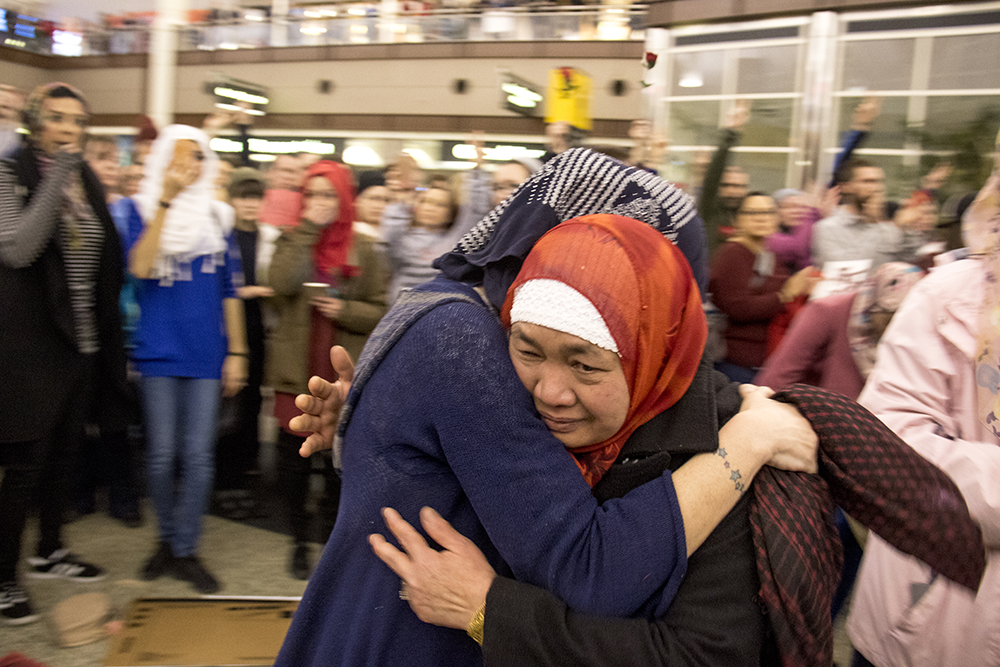 Desiree Winess (left) comforts dismayed Samoah Soulong during protests at DIA, Jan. 28, 2017. (Kevin J. Beaty/Denverite)  amal kassir; immigration; refugees; politics; protest; copolitics; rally; dia; denver; colorado; kevinjbeaty;