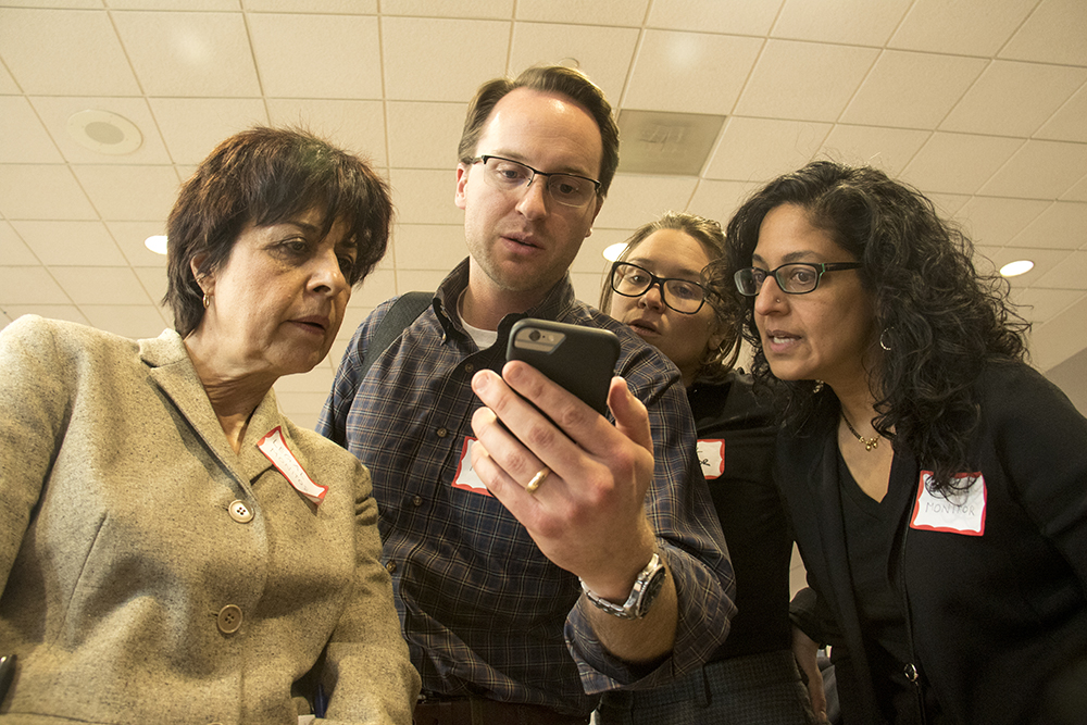 A quad of lawyers respond to texts from family members of people who could be held up in customs at DIA. A pop-up, pro-bono law office at DIA. Jan. 28, 2017. (Kevin J. Beaty/Denverite)  immigration; refugees; politics; protest; copolitics; rally; dia; denver; colorado; kevinjbeaty