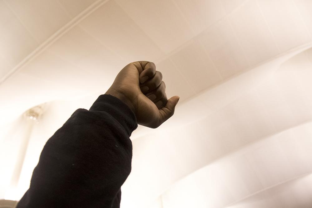 Jumoke Emery raises a fist during protests at DIA. Jan. 28, 2017. (Kevin J. Beaty/Denverite)  immigration; refugees; politics; protest; copolitics; rally; dia; denver; colorado; kevinjbeaty
