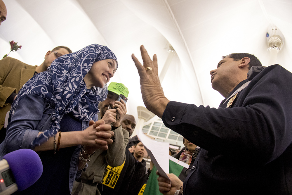 Amal Kassir talks to DIA police Commander Tony Lopez, who tells her that first amendment expression in the airport is prohibited without a permit. Protests at DIA. Jan. 28, 2017. (Kevin J. Beaty/Denverite)  immigration; refugees; politics; protest; copolitics; rally; dia; denver; colorado; kevinjbeaty