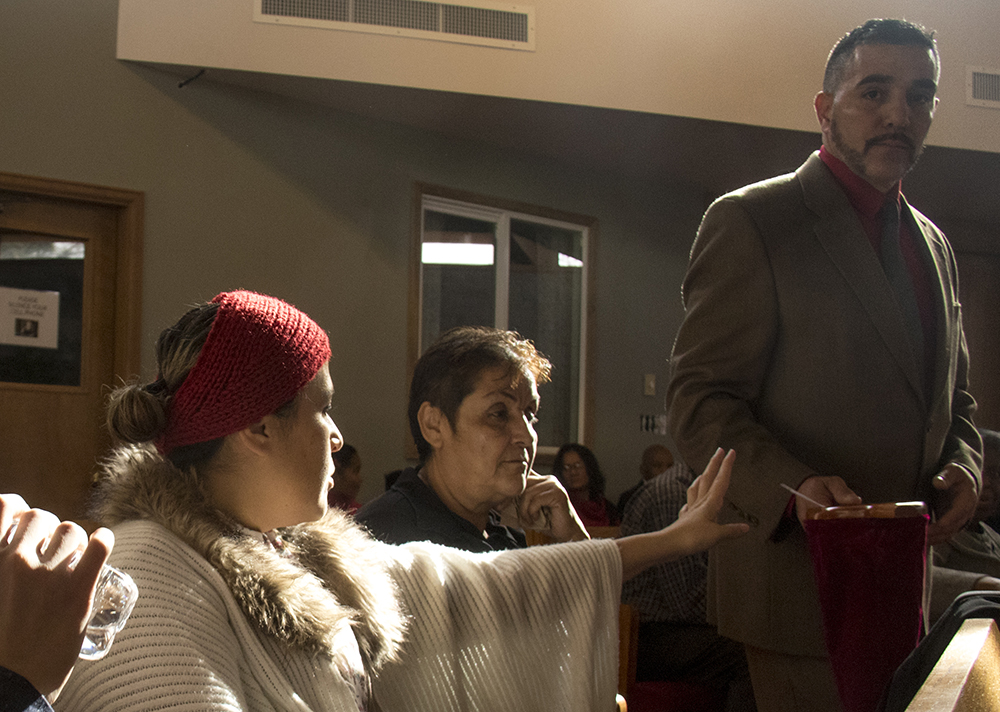 Isidro Quintana collects tithes as his wife, Erica, sits in a pew with her mother and their son. at Seventh Day Adventist Church Reform Movement, Jan. 28, 2017. (Kevin J. Beaty/Denverite)  isidro quintana; kevinjbeaty; denverite; denver; colorado; immigration; deportation; church; worship; faith; first adventist;