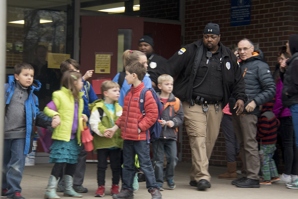 Bromwell Elementary School security guards lead students out of the building after a standoff between a would-be carjacker and police on 3rd Avenue locked the school down. (Kevin J. Beaty/Denverite)  crime; police; denver; cherry creek; denverite; kevinjbeaty; colorado