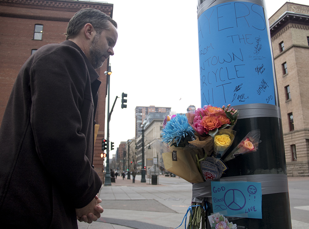 Ryan Neville places flowers at a memorial for RTD security guard Scott Von Lanken near Union Station, Feb. 1, 2017. (Kevin J. Beaty/Denverite)  union station; scott von lankin; memorial; denverite; denver; colorado; kevinjbeaty;