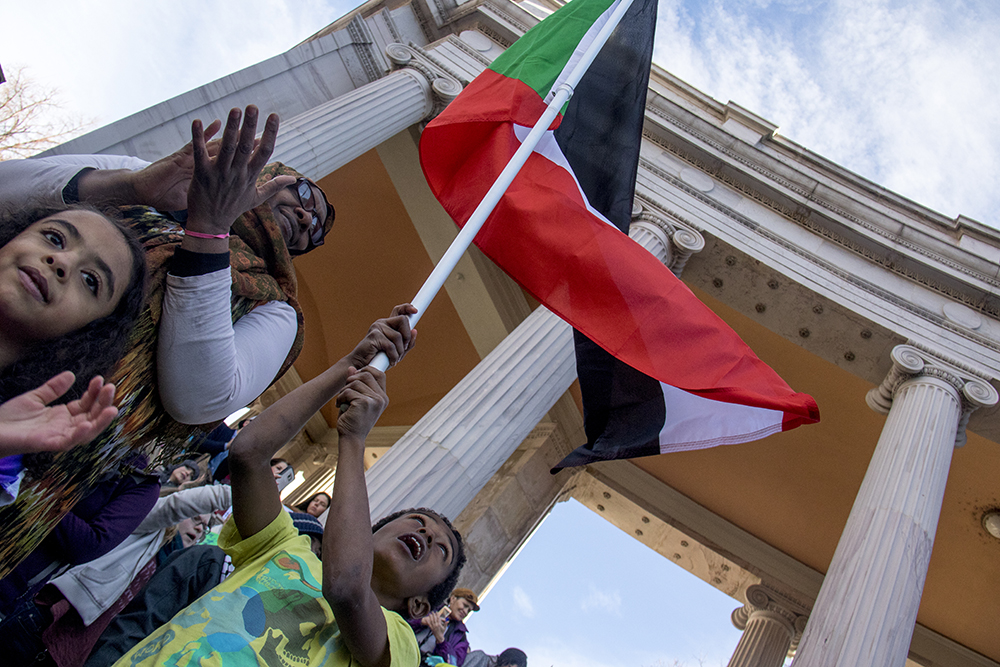 Hassam Hashim holds up the Sudanese flag with his mother Rehab and sister Selma. The Protect Our Muslim Neighbors Rally at Civic Center Park, Feb. 4, 2017. (Kevin J. Beaty/Denverite)  march; protest; muslim neighbors; civic center park; copolitics; kevinjbeaty; denver; denverite;