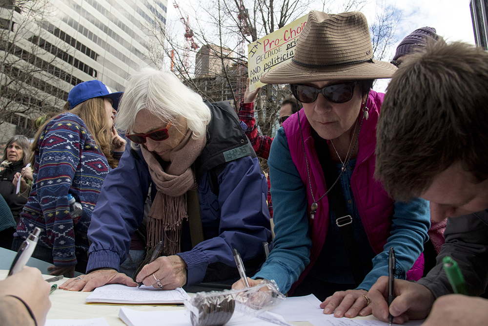 Eve Booth (left) and Karin Koerperich write letters to Senator Cory Gardner. A rally in support of Planned Parenthood at Skyline Park, Feb. 11, 2017. (Kevin J. Beaty/Denverite)  rally; planned parenthood; abortion; protest; copolitics; skyline park; denver; kevinjbeaty; denverite; colorado