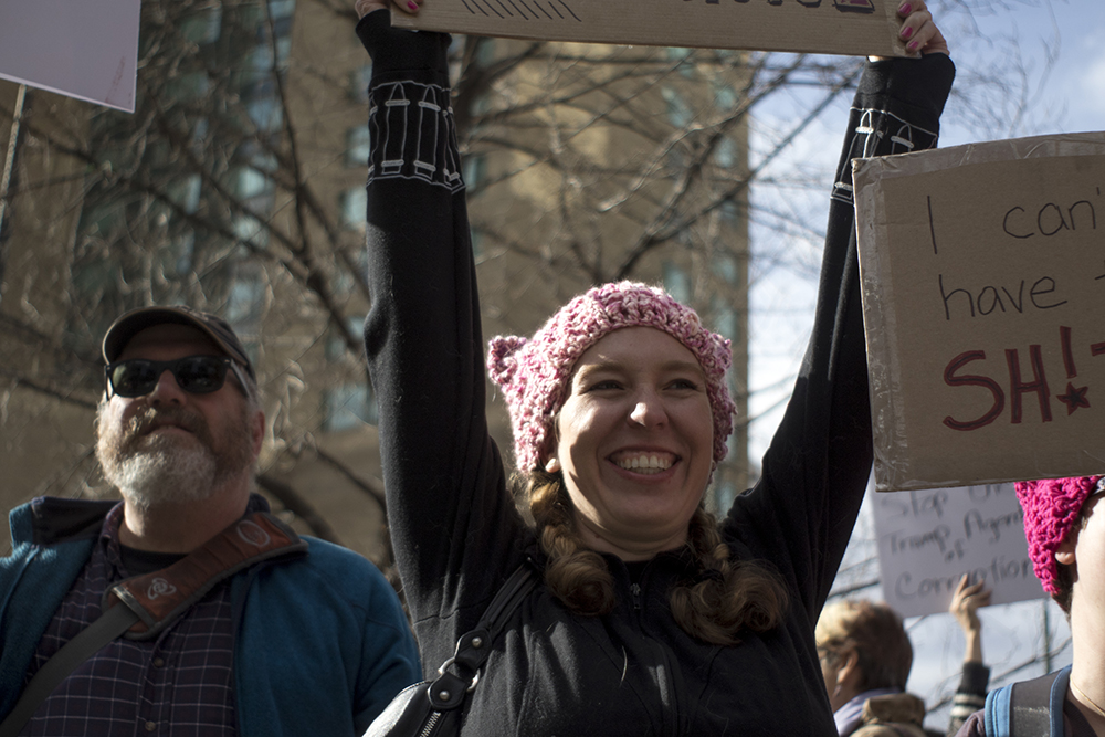 Ana Holmes holds up protest signs along Arapahoe Street. A rally in support of Planned Parenthood at Skyline Park, Feb. 11, 2017. (Kevin J. Beaty/Denverite)  rally; planned parenthood; abortion; protest; copolitics; skyline park; denver; kevinjbeaty; denverite; colorado