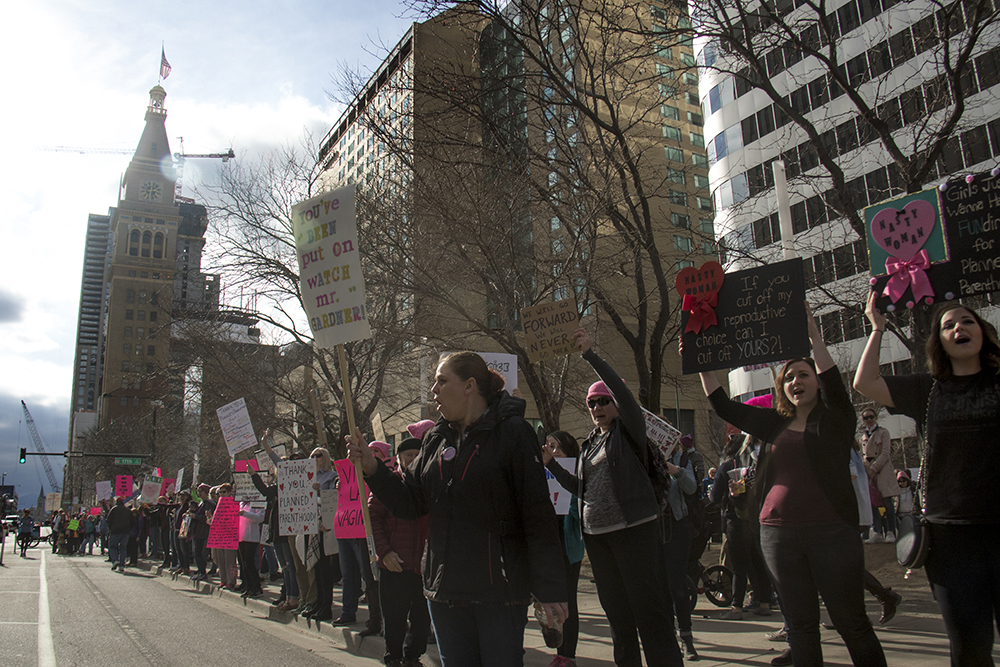 Protesters hold up signs along Arapahoe Street. A rally in support of Planned Parenthood at Skyline Park, Feb. 11, 2017. (Kevin J. Beaty/Denverite)  rally; planned parenthood; abortion; protest; copolitics; skyline park; denver; kevinjbeaty; denverite; colorado